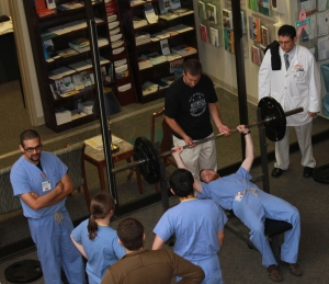 University of Tennessee College of Medicine Chattanooga and Erlanger Health System participants circle the bench press area as one of the medical residents attempt to lift weight during the completion.